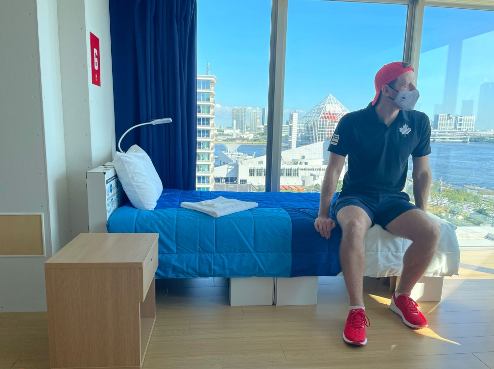 Male athlete sits on cardboard bed in his room in Team Canada building