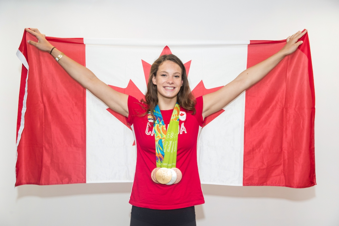 A photo of Penny Oleksiak in a red t-shirt wearing four Olympic medals and holding a Canadian flag.