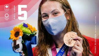 Penny Oleksiak holding her medal and flowers