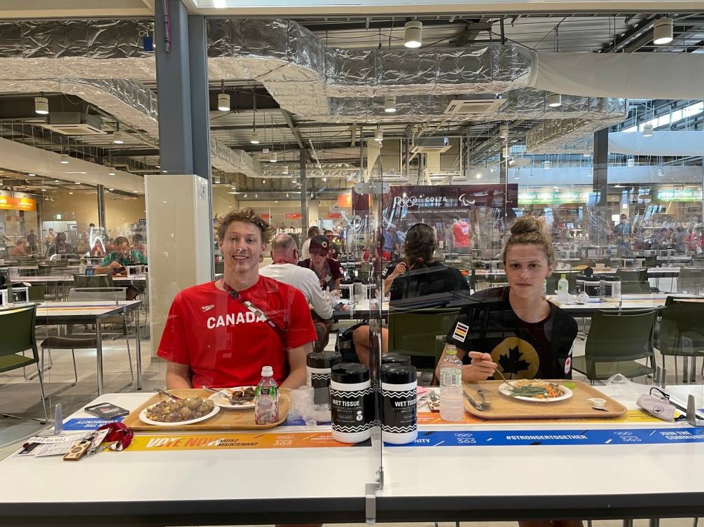 Male and female athlete sitting at dining hall table with plexiglass divider between them