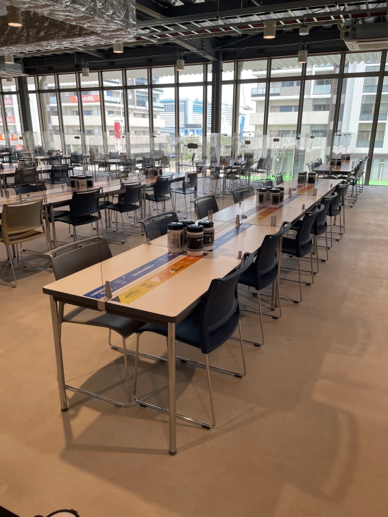 Tables and chairs set up in a dining hall with plexiglass dividers