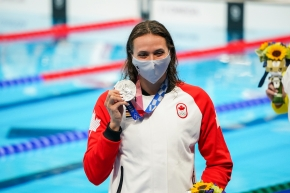 Kylie Masse, wearing a Canada jacket and protective mask, holds up her silver medal in front of the pool.