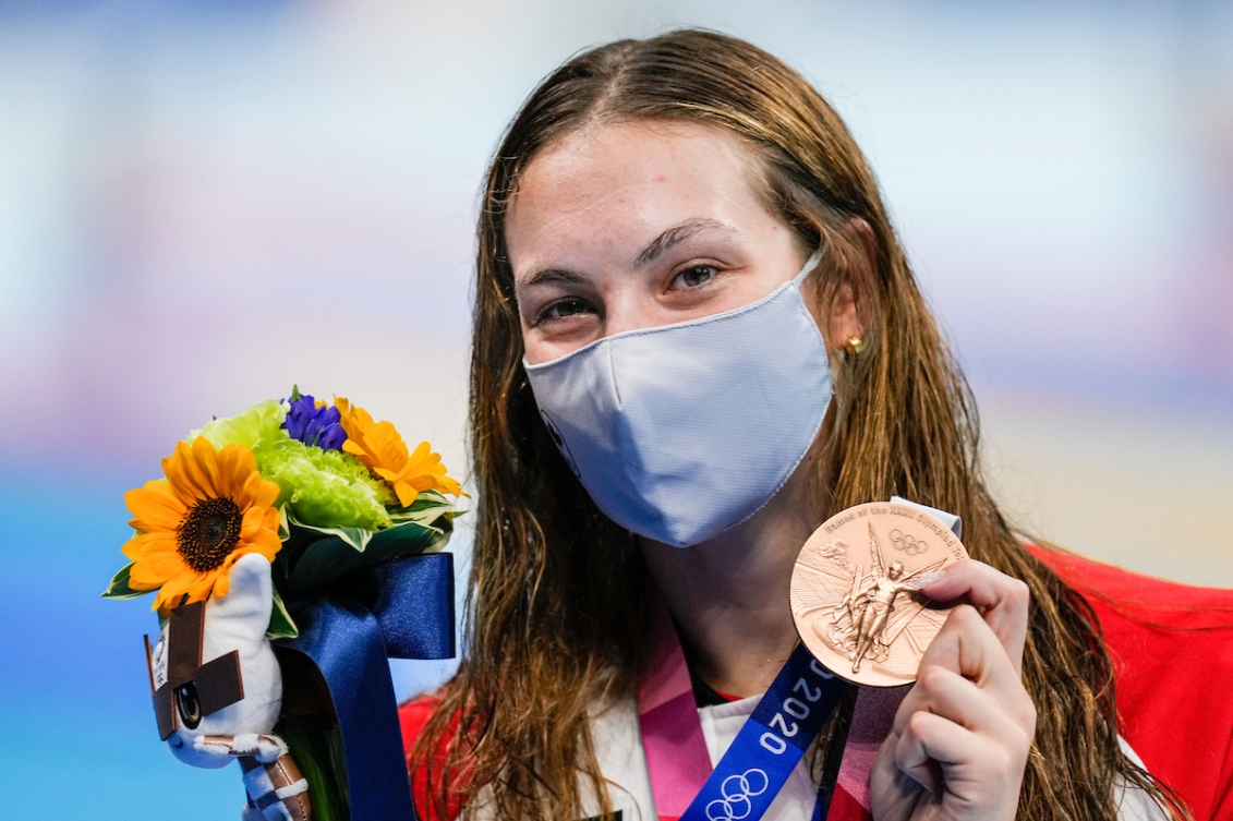 Penny Oleksiak, wearing a Canada jacket and protective mask, holds up a bouquet of flowers and her bronze medal