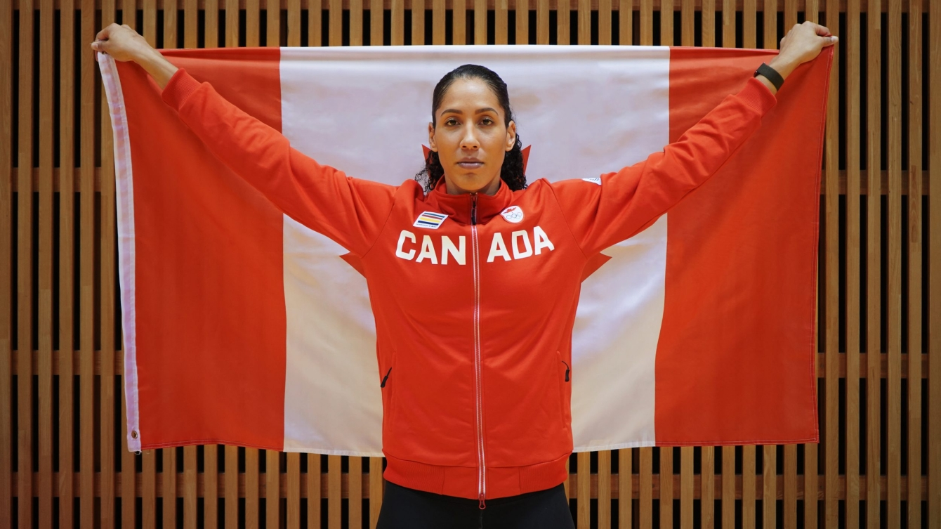 Miranda Ayim holds a Canadian flag behind her