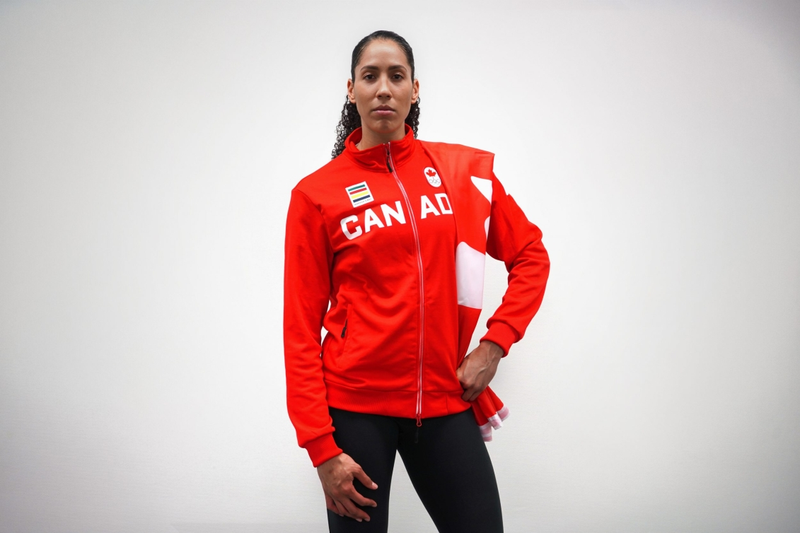 Miranda Ayim poses with Canadian flag draped over shoulder