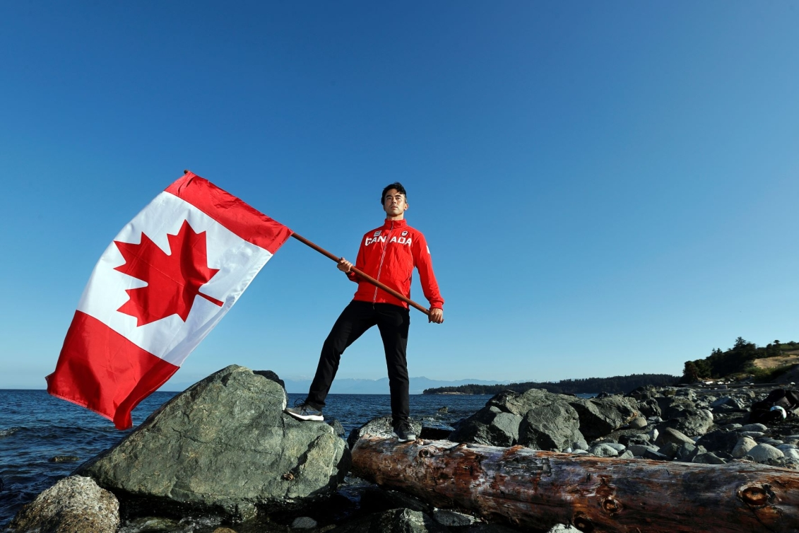Nathan Hirayama holds Canadian flag by water