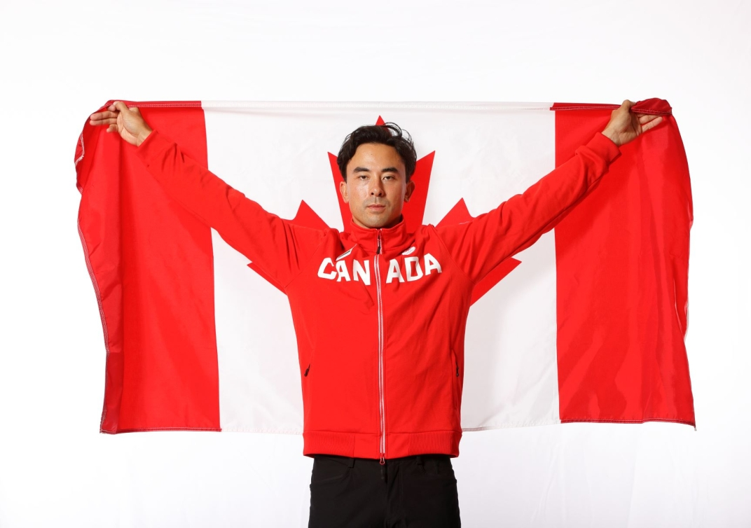 Nathan Hirayama holds Canadian flag over shoulders