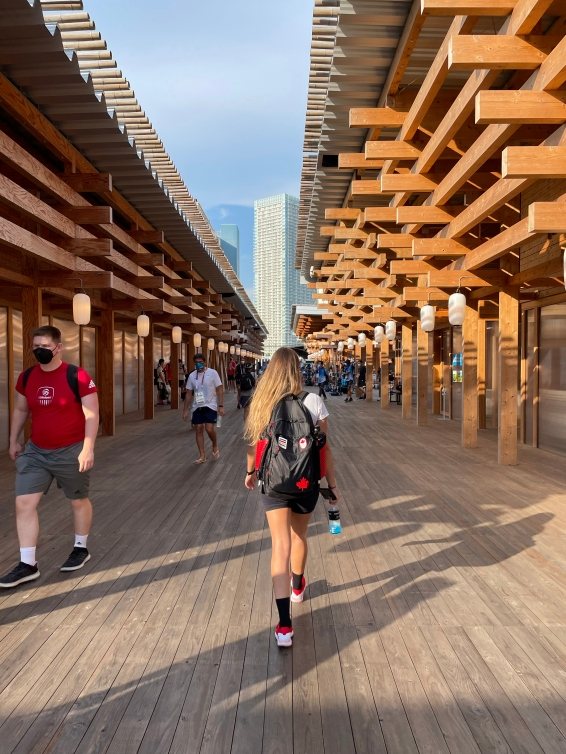 Athletes walk between buildings in the Olympic Village with the buildings created with wood larch