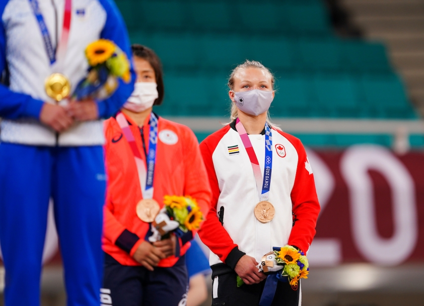 Jessica Klimkait stands with her bronze medal wearing her Team Canada jacket and mask.