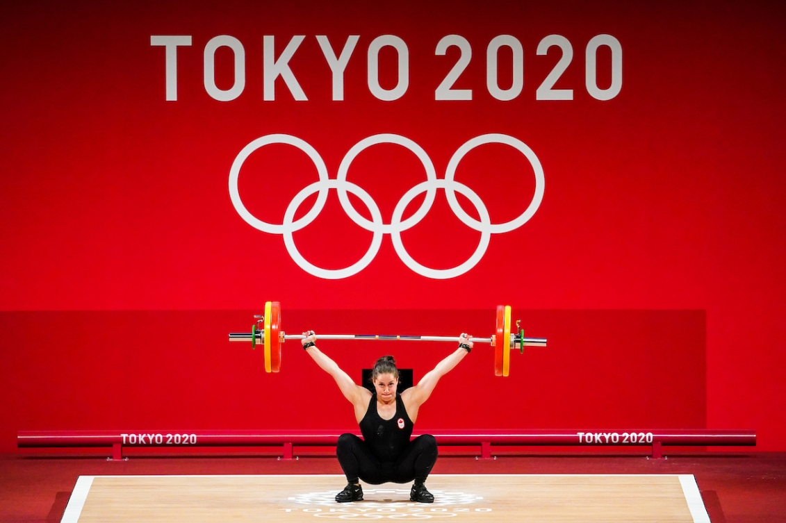 Maude Charron squats with the bar above her head and a large image of the Olympic rings on a wall behind her.