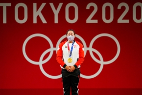 Weightlifter Maude Charron stands with her eyes closed, gold medal around her neck, in front of a wall reading Tokyo 2020.