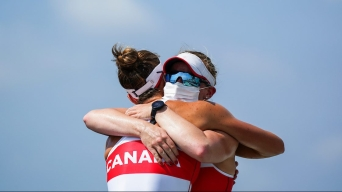 Rowers Caileigh Filmer and Hillary Jenssens, wearing sunglasses and protective masks, hug in celebration against the backdrop of a clear blue sky.