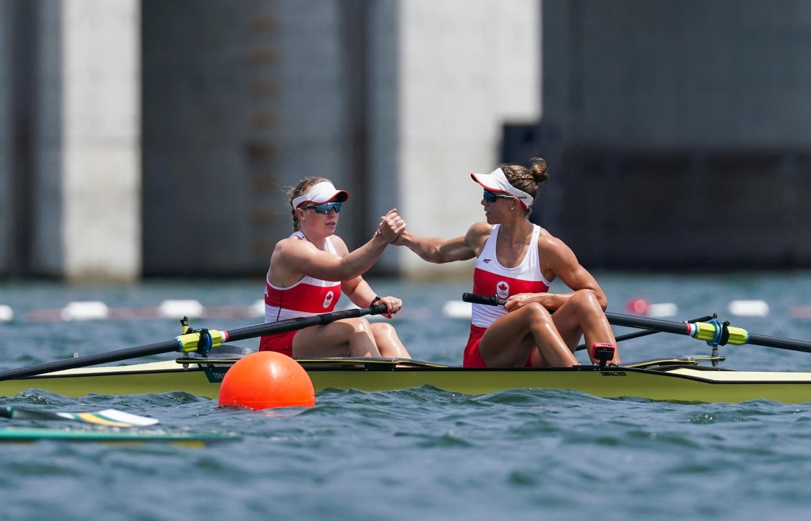 Two rowers shake hands after a race