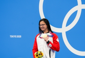 Maggie Mac Neil holds up gold medal on podium