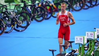 Matt Sharpe runs through the transition area of a triathlon
