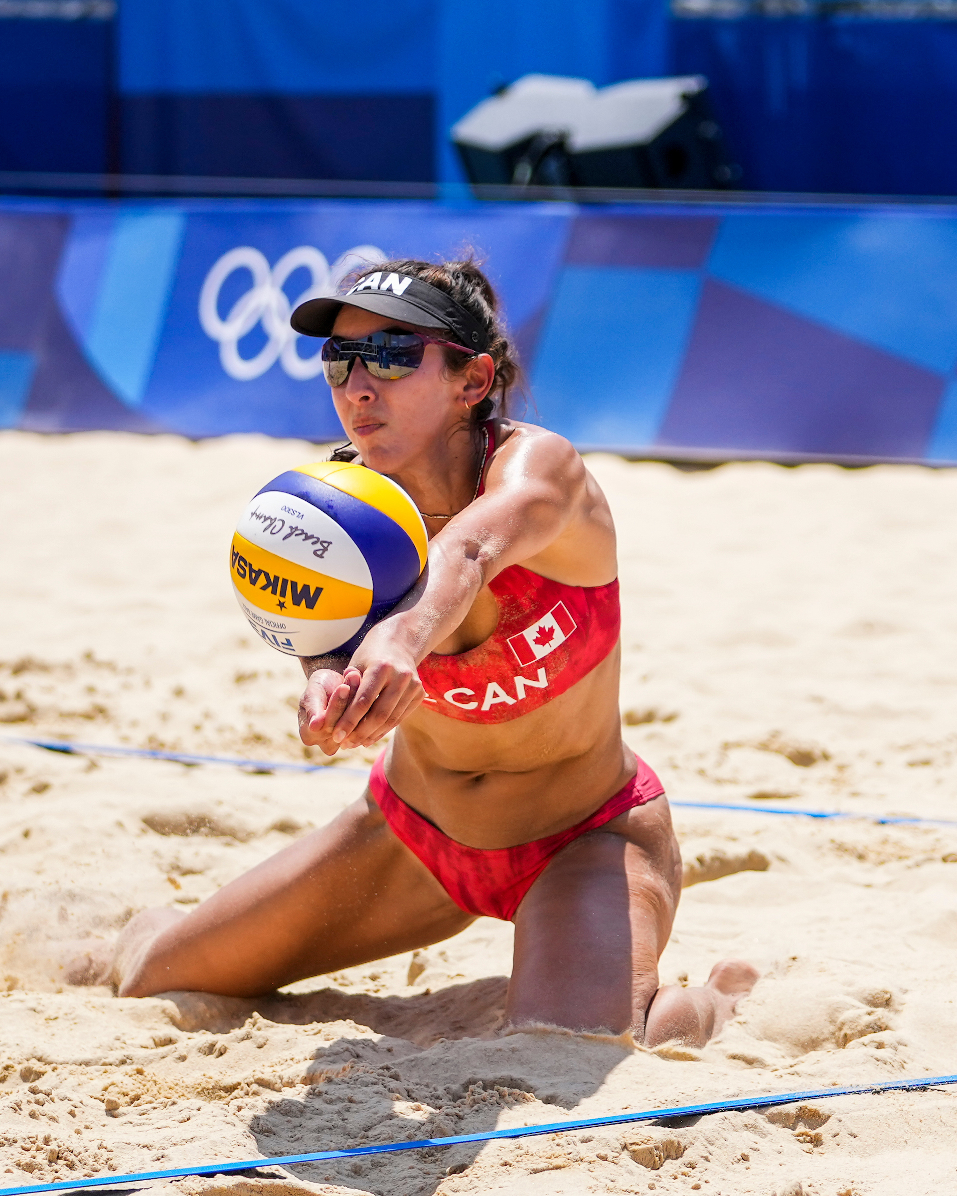 Beach volleyball player digs for a ball