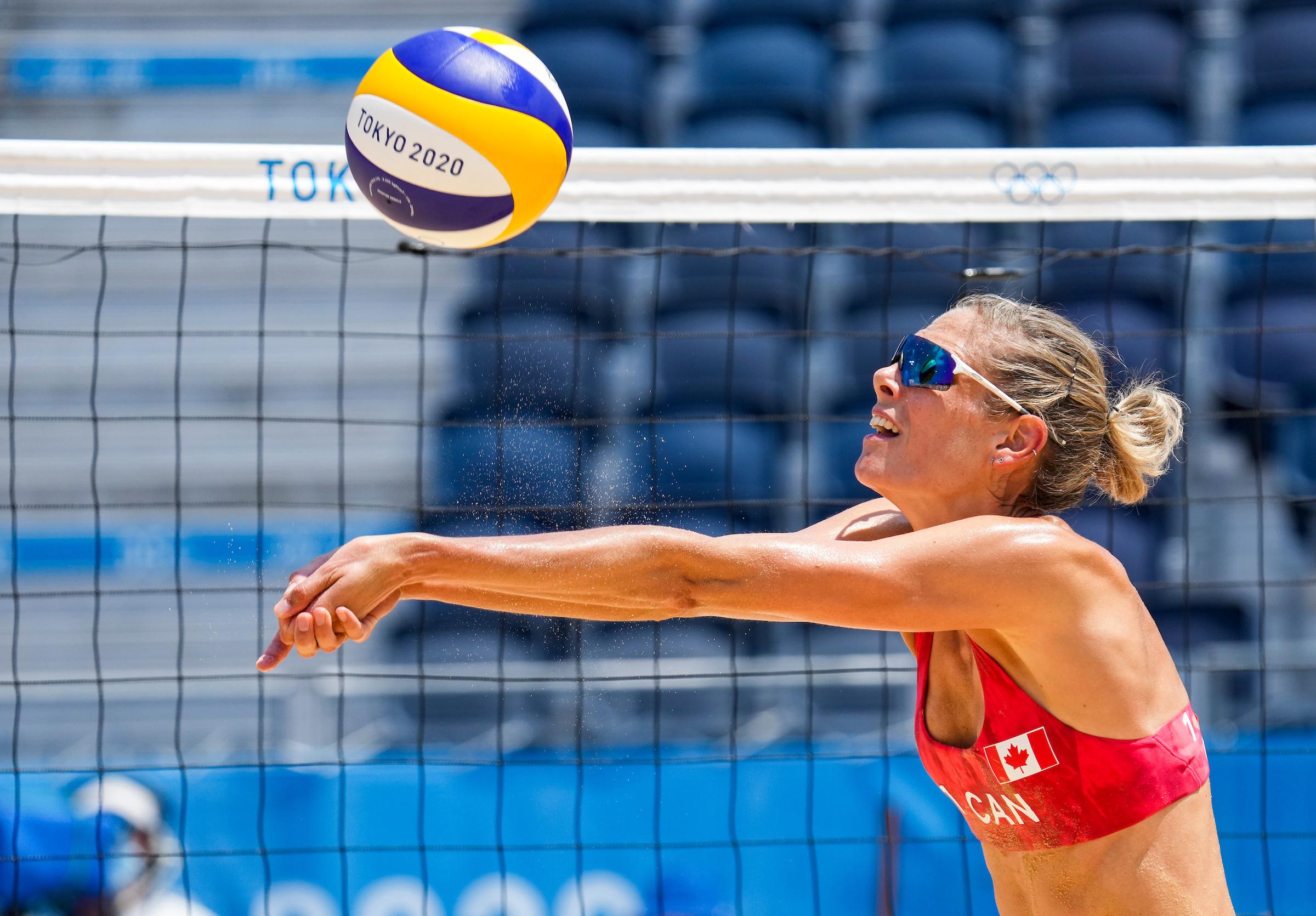 Beach volleyball player bumps a ball
