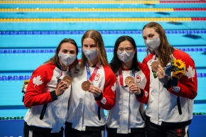Canadian swimmers holding their bronze medals and flowers by the poolside