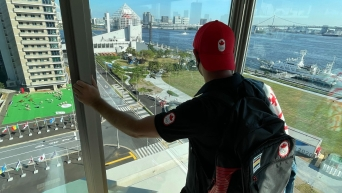 A man wearing a Team Canada baseball cap backwards looks out at the view of Tokyo Bay.