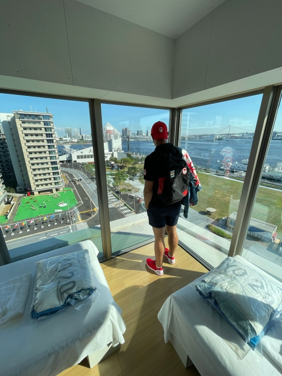 male athlete look out on view of Tokyo from bedroom window in a high rise