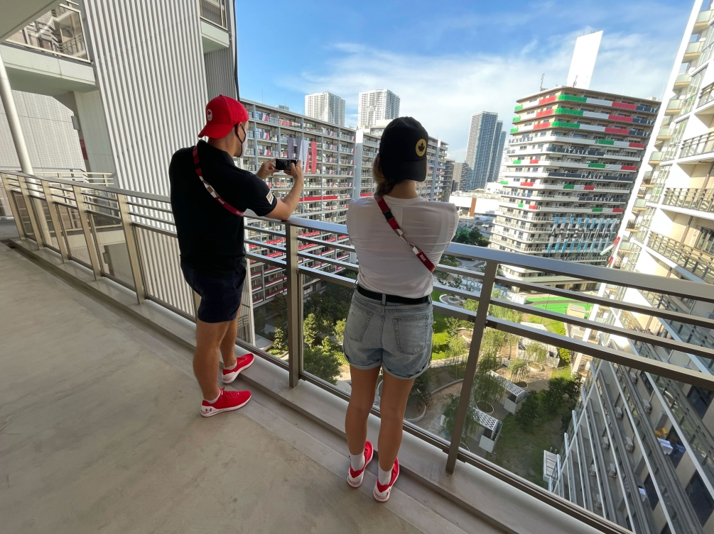 Male and female athlete stand on balcony overlooking views of athlete's village