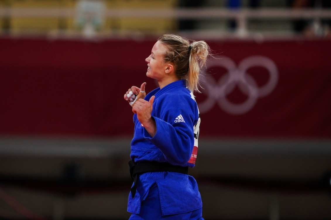 female athlete puts thumb us while walking off the mat