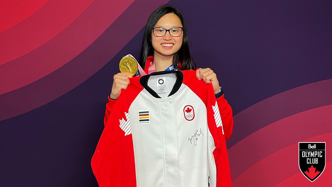 girl stands in front of red backdrop holding a white jacket and a gold medal