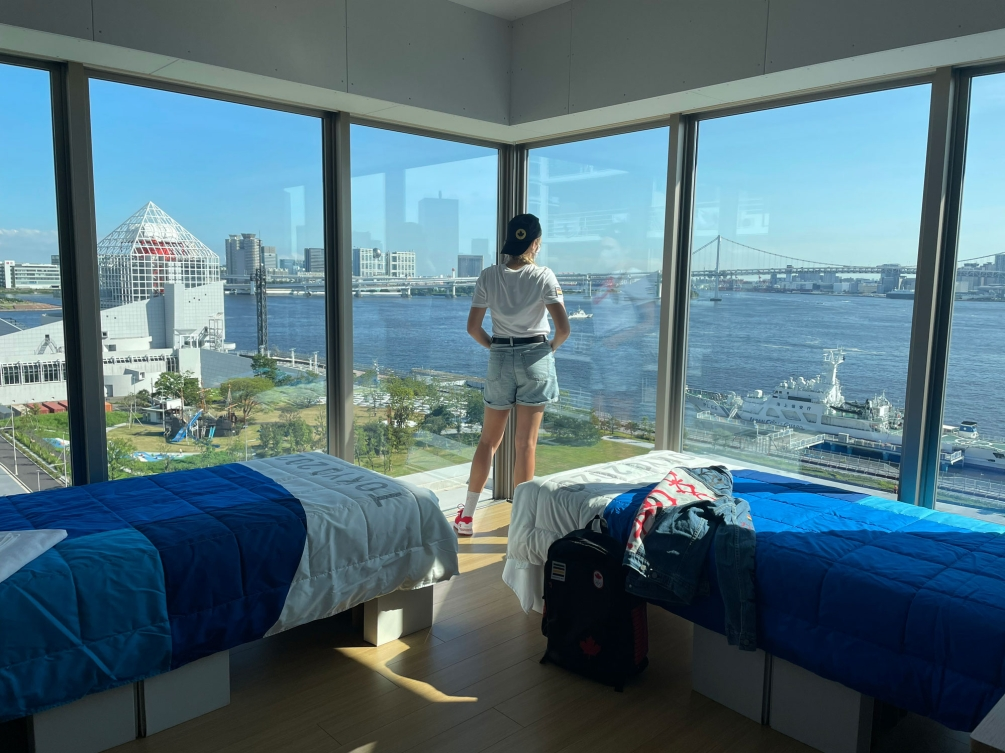Female athlete checks out the view from her housing window out on the Tokyo scenery