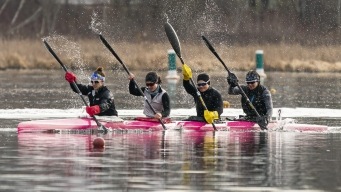 Four female kayakers paddling in their boat