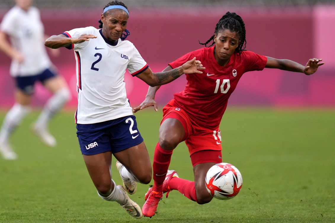 Ashley Lawrence and Crystal Dunn fight for the ball