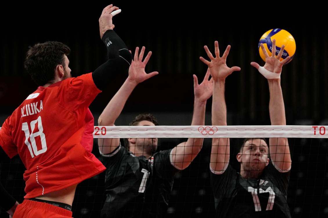 Two Canadians try to block an ROC player's spike