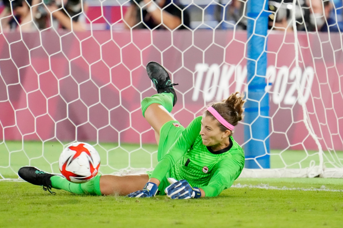 Stephanie Labbe dives to stop a penalty kick