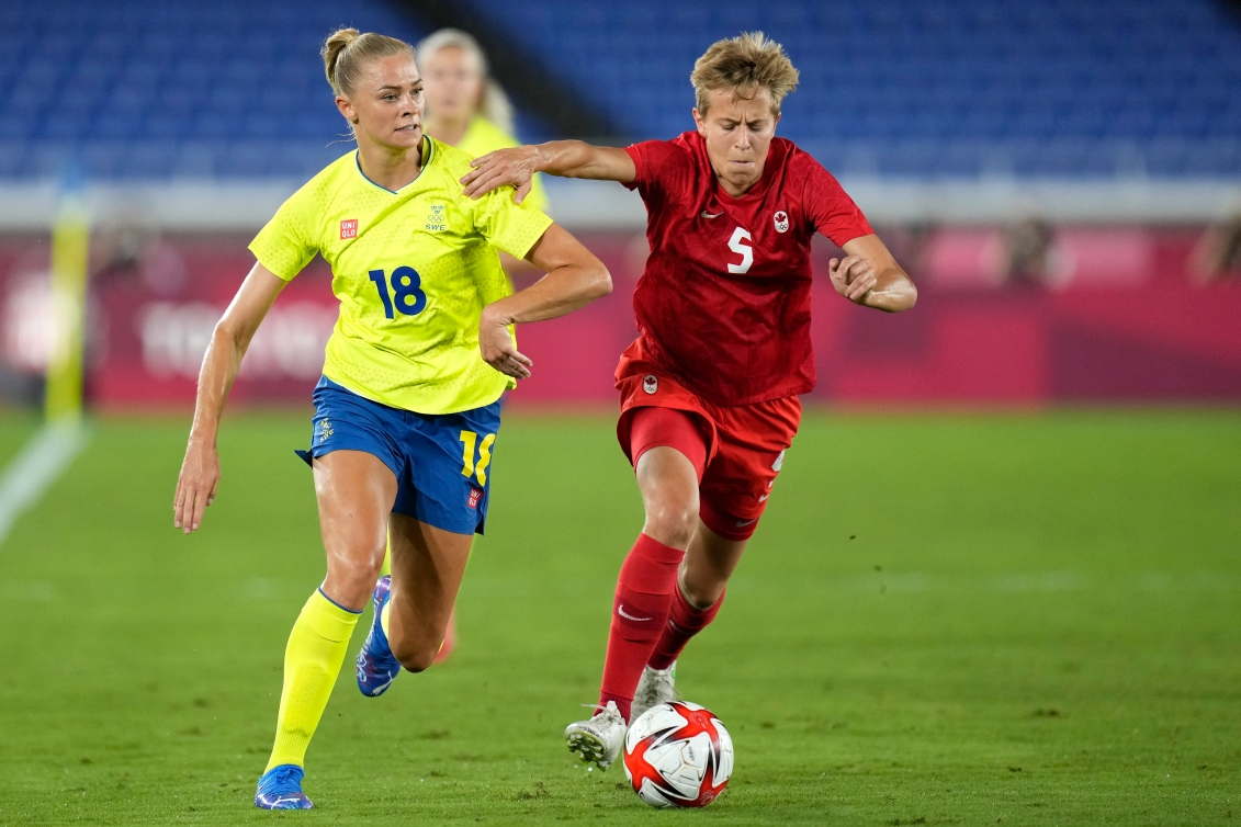 Quinn battles for the ball with a Swedish opponent