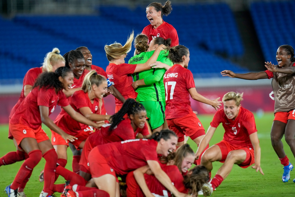 Team Canada celebrates on the field following the win