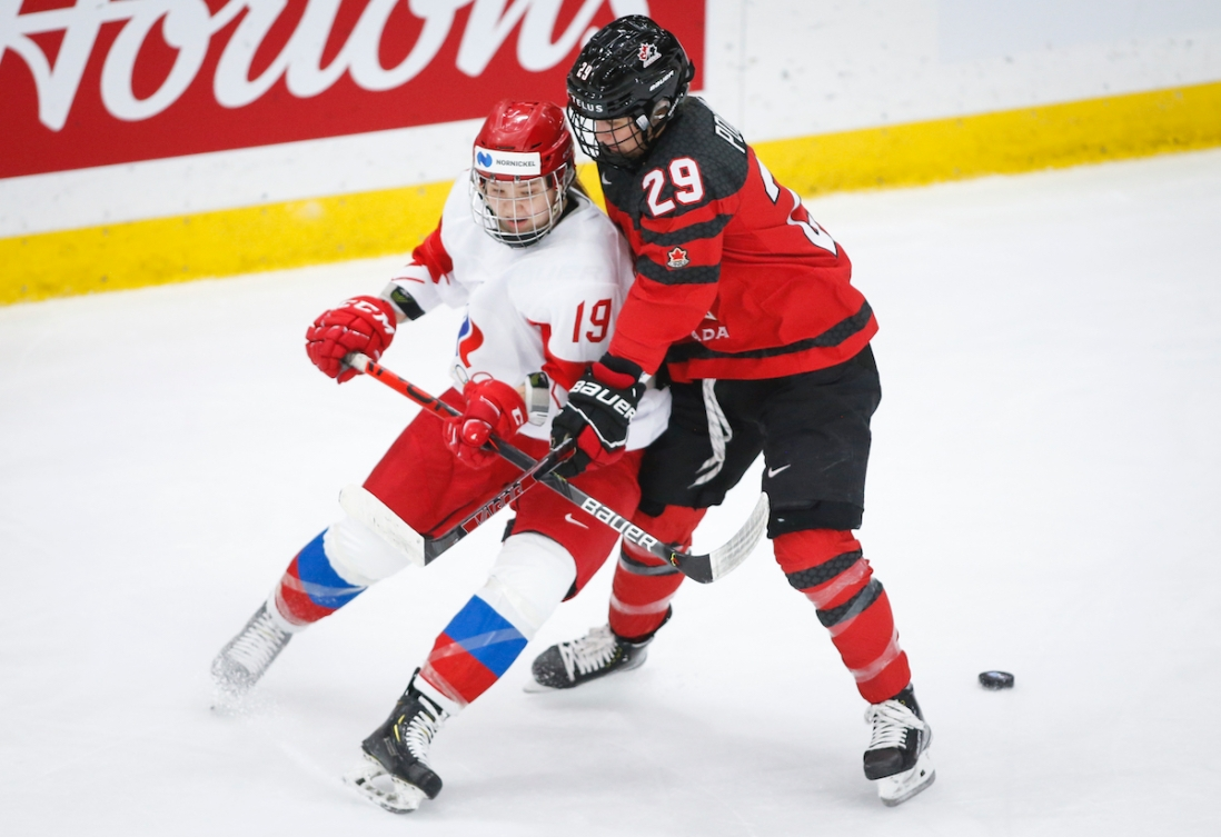 Russia's Yelena Provorova, left, is is checked by Canada's Marie-Philip Poulin during first period IIHF Women's World Championship hockey action in Calgary, Alta., Sunday, Aug. 22, 2021. THE CANADIAN PRESS/Jeff McIntosh