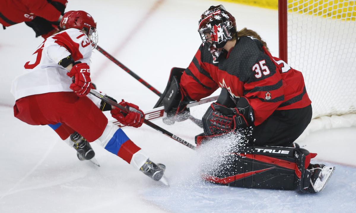 Russia's Viktoria Kulishova, left, has her shot blocked by Canada's goalie Ann-Renee Desbiens during second period IIHF Women's World Championship hockey action in Calgary, Alta., Sunday, Aug. 22, 2021. THE CANADIAN PRESS/Jeff McIntosh