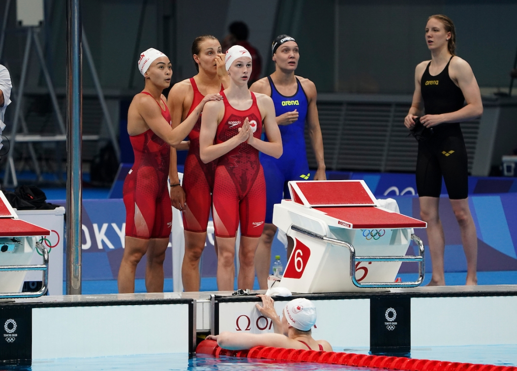 Canadian swimmers stand on the deck watching the score board