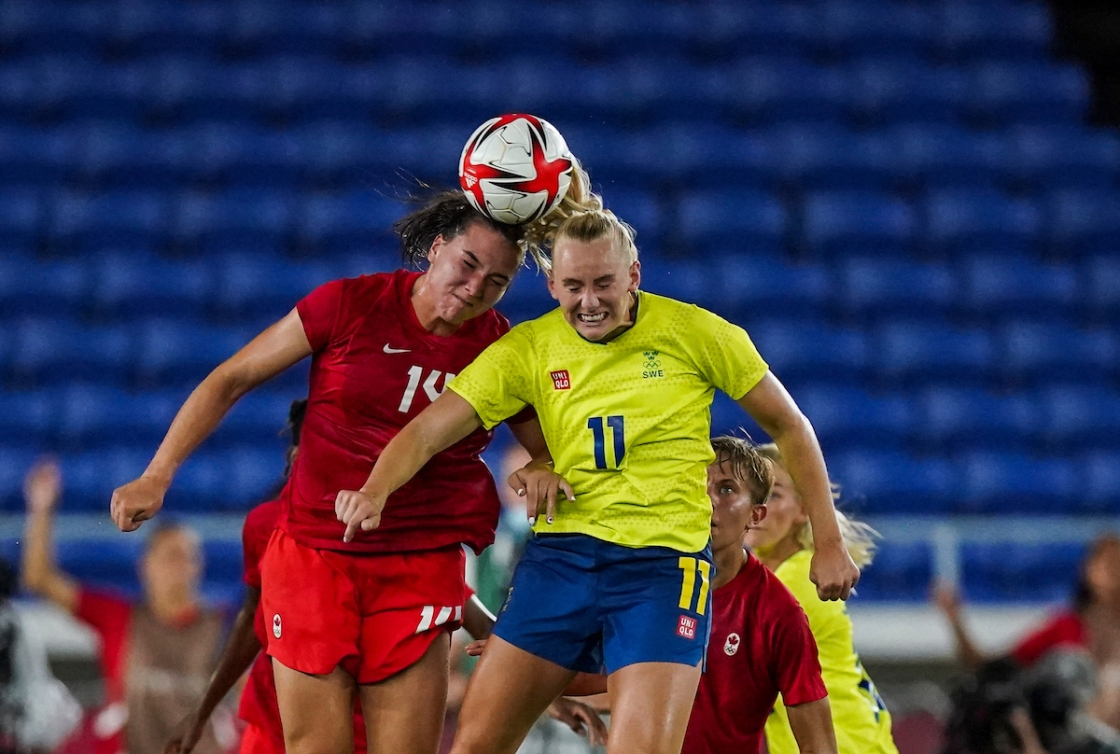Vanessa Gilles and a Swedish player both go for a header on the ball