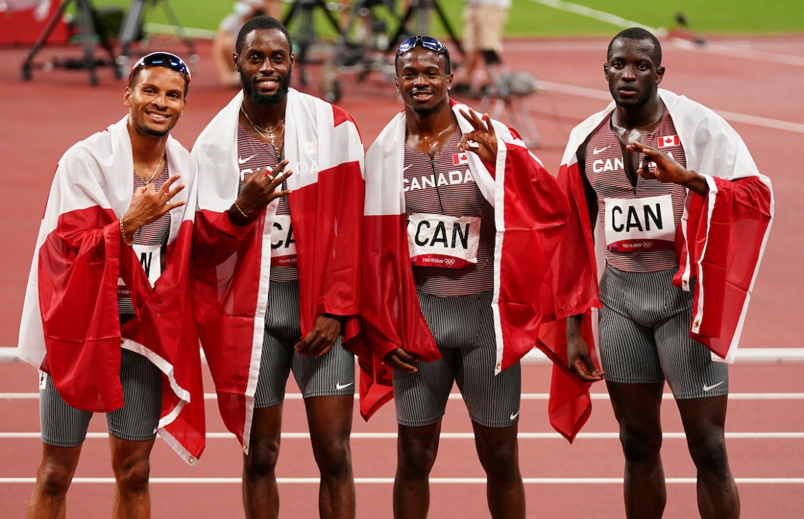 Canada's men's 4x100m relay team poses with the Canadian flag