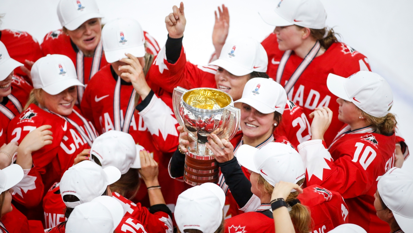 Marie-Philip Poulin holds up the trophy while surrounded by her teammates.