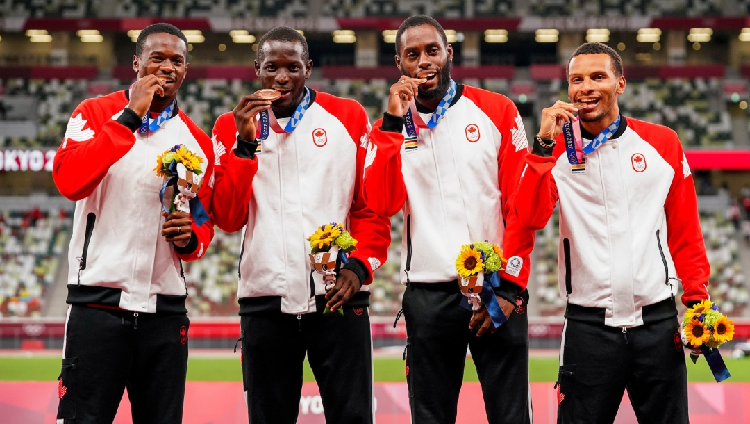 Men's 4x100m relay team bite their medals on the podium