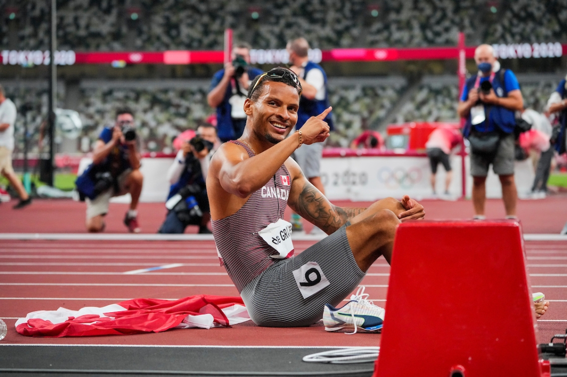 Andre De Grasse poses for the camera at the finish line