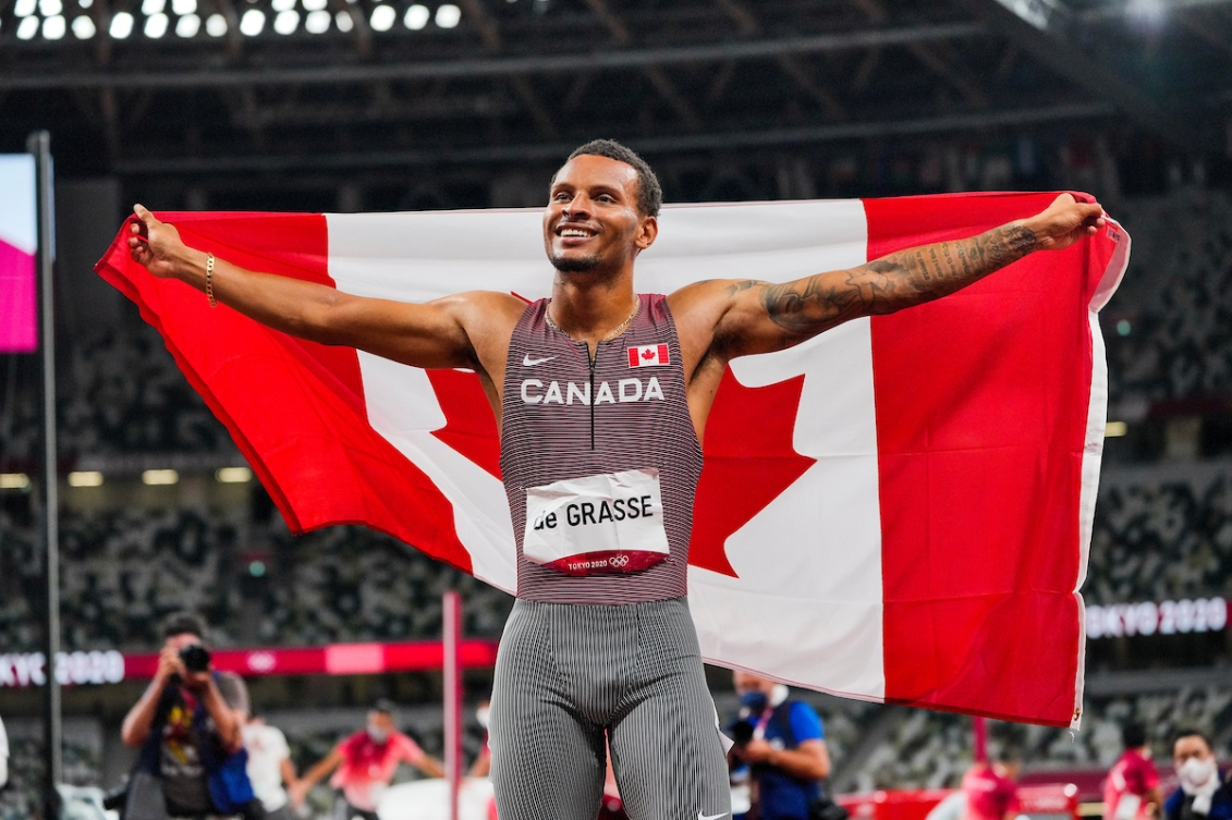 Andre De Grasse raises the Canadian flag after winning the 200-metre final