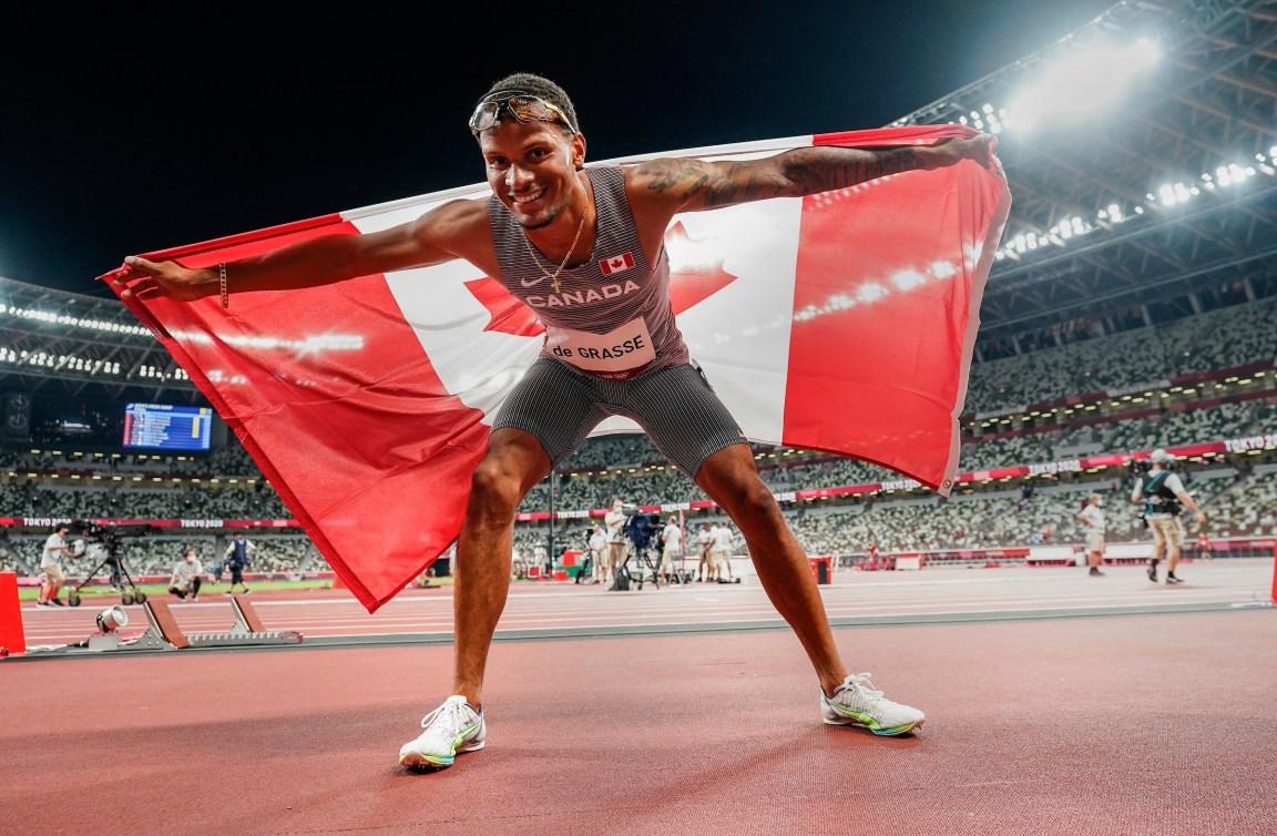 Andre De Grasse holds the Canadian flag in celebration