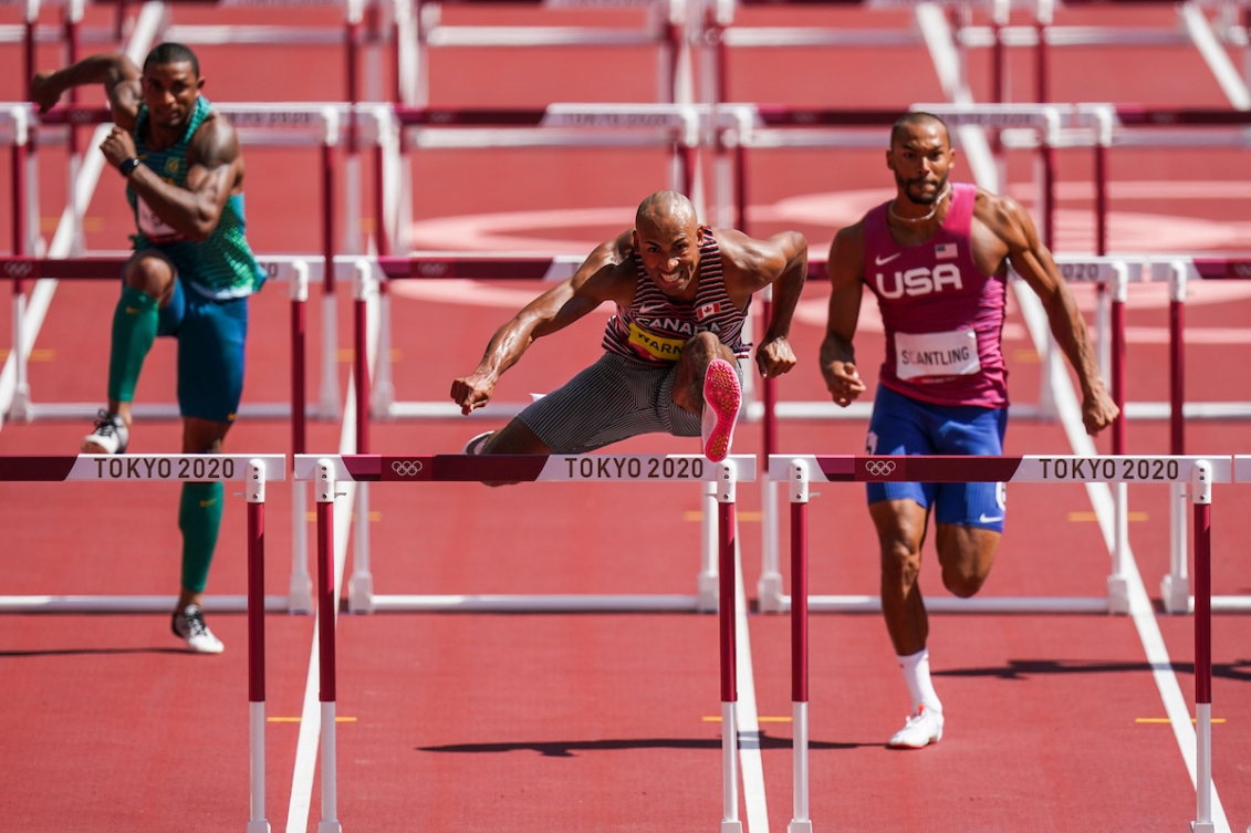 Damian Warner races over the 110-metre hurdles in the decathlon.