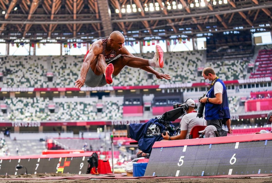 Damian Warner in mid air while doing a long jump