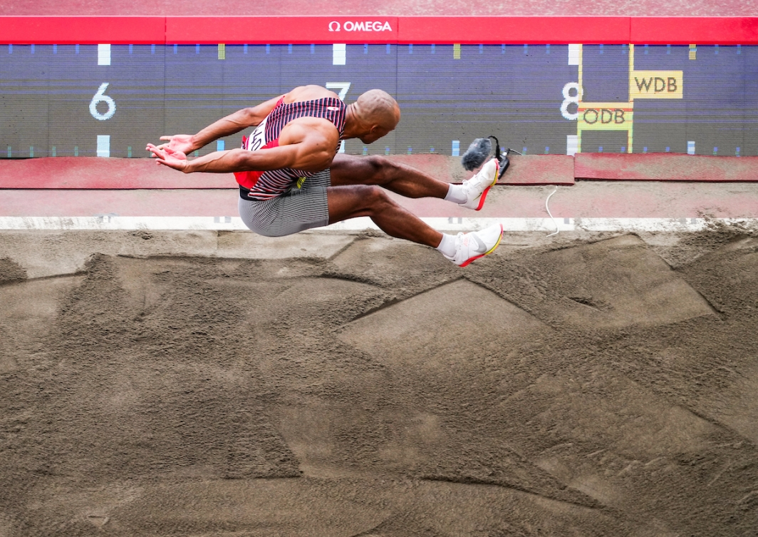 Overhead shot of Damian Warner in air over long jump sand pit