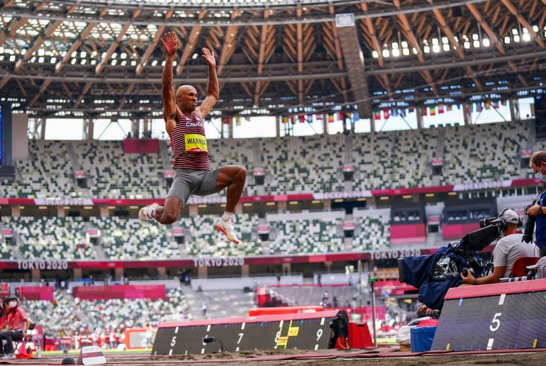 Damian Warner in mid air doing long jump
