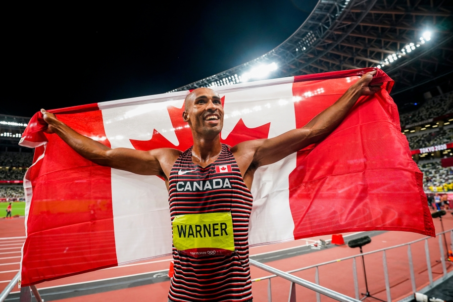 Damian Warner holds Canadian flag over shoulders