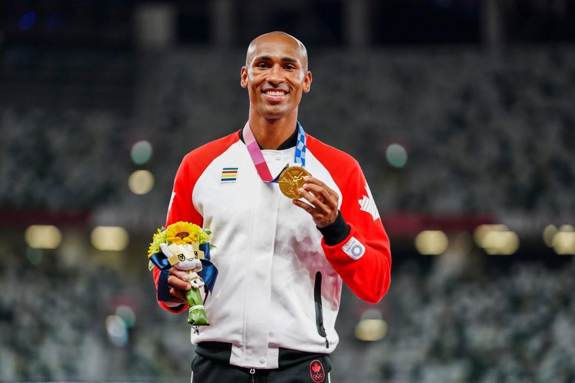 Damian Warner smiles on the podium wearing his gold medal